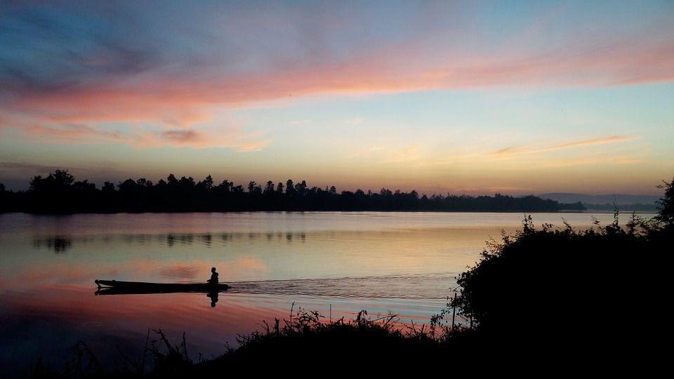 силуэт человека в лодке на утренней реке